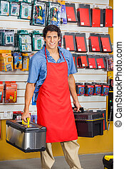 Salesman Holding Toolboxes In Hardware Shop