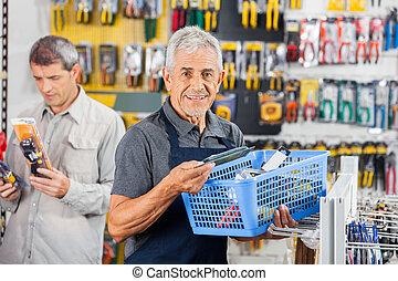Salesman Holding Tools Basket At Hardware Store