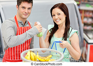 salesman in a grocery store giving apples to his smiling female customer both looking at the camera