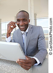 Salesman on business travel using electronic tablet