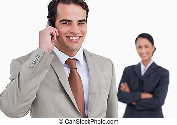 Salesman on his cellphone with colleague behind him