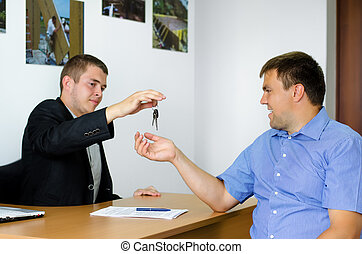 Salesman or agent handing keys to a client