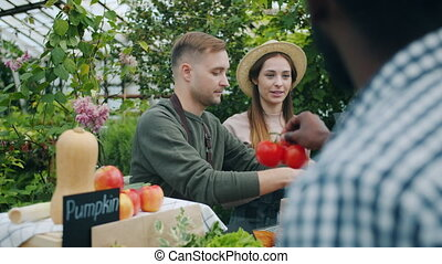 Salesman packing vegetables in paper bag during farm sale...