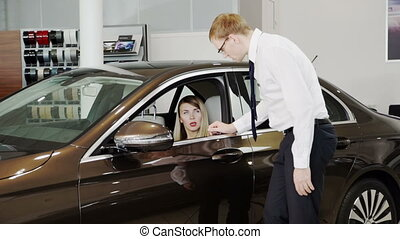 Salesman presenting executive class car to woman inside of show room.