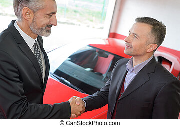 salesman shaking hands with client after selling him a car