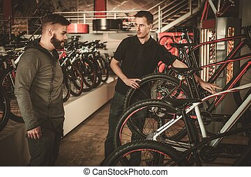 Salesman showing a new bicycle to interested customer in...