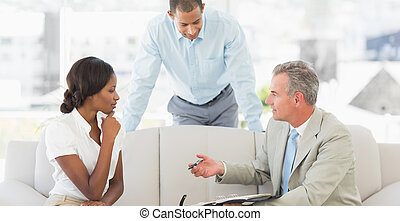 Salesman showing clients where to sign the deal in the...