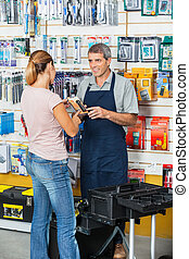Salesman Showing Flashlight To Customer In Hardware Store