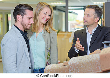 Salesman showing roof tiles to couple in showroom