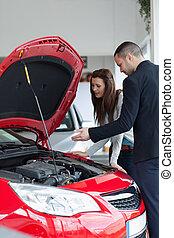 Salesman showing the car engine