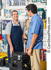 Salesman Showing Tool Case To Customer In Store
