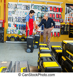 Salesman Showing Tool Cases To Customer In Store