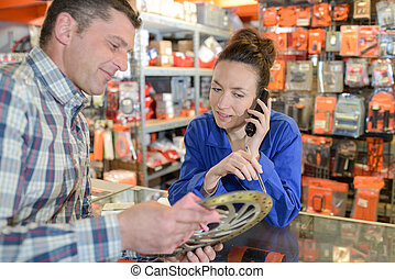 salesman showing tools to female customer in hardware shop
