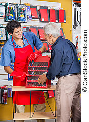 Salesman Showing Tools To Senior Man In Store