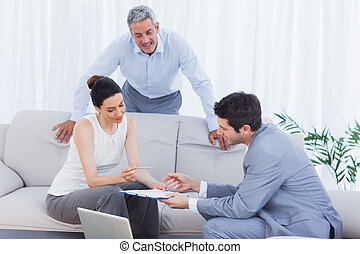Salesman speaking with customers on couch