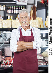 Salesman Standing Arms Crossed In Grocery Store