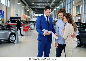 Salesman talking to a young couple at the dealership...