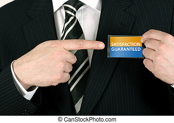 Business man making a sale pointing to a satisfaction guaranteed badge