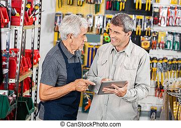 Salesman With Customer Using Digital Tablet In Store
