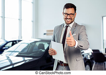 Salesperson at car dealership selling vehicles