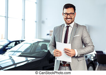 Salesperson at car dealership selling vehicles