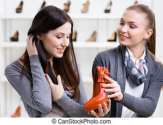 Salesperson offers footwear for the customer - Salesperson...