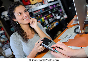 saleswoman accepting payment from customer in store