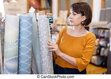 Saleswoman arranging fabric bolts