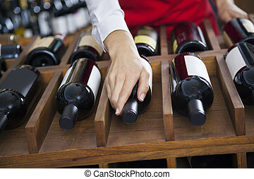 Saleswoman Arranging Wine Bottles In Rack - Cropped image of...