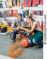 Saleswoman Assisting Customer In Using Air Compressor