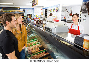 Saleswoman Attending Customers At Butcher's Shop - Smiling...