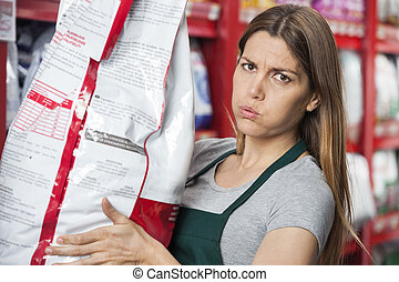 Saleswoman Carrying Heavy Food Package In Pet Store -...