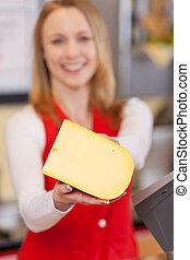 Saleswoman Displaying Cheese In Grocery Store