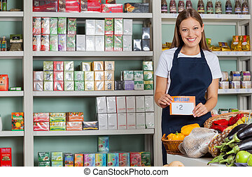 Saleswoman Displaying Pricetag In Grocery Store - Portrait...