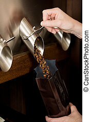 saleswoman filling coffee beans in bag