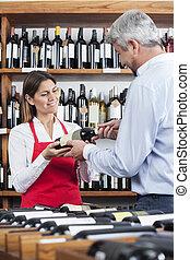 Saleswoman Giving Wine Bottle To Male Customer