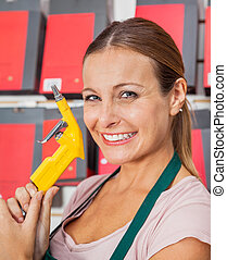 Saleswoman Holding Air Compressor Hose In Shop