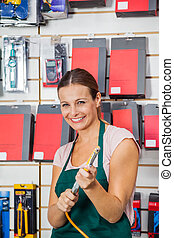 Saleswoman Holding Air Compressor Hose In Store