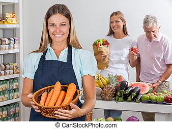 Saleswoman Holding Carrot Basket At Supermarket - Portrait...