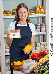Saleswoman Holding Pricetag And Bellpepper In Supermarket
