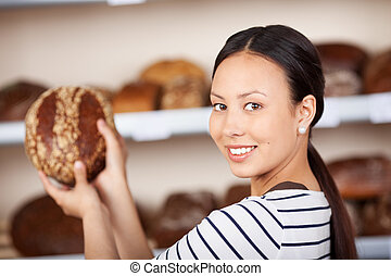 saleswoman holding wholemeal bread in bakery