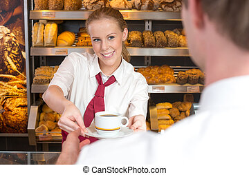 Saleswoman in baker's shop giving cup of coffee to customer...