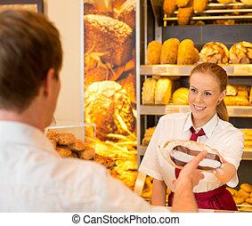 Saleswoman in bakery selling bread to customer - Shopkeeper ...