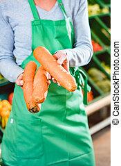 Saleswoman in organic supermarket offering fresh carrots