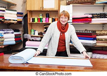 saleswoman measures the fabric - saleswoman measures the...