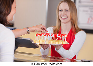 Saleswoman Offering Cheese Blocks With Swiss Flag To...
