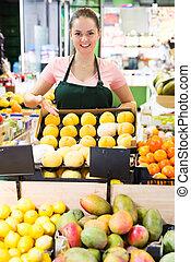 Saleswoman offering peaches in supermarket