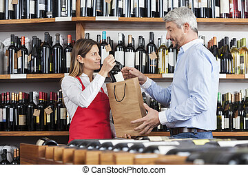 Saleswoman Putting Wine Bottle In Paperbag For Customer -...