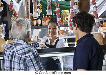 Saleswoman Selling Cheese To Customers At Shop