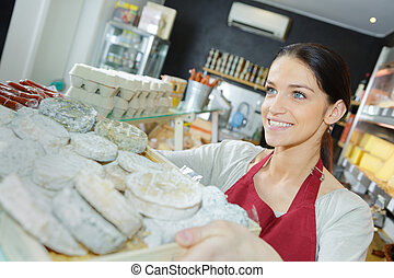 saleswoman selling cheese to man in grocery store